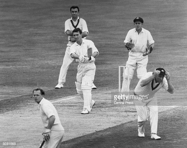 England cricketer Fred Titmus hits a six at the Oval aginst Australia during the 5th Test Match. Looking on are Australians, Bobby Simpson, at first...