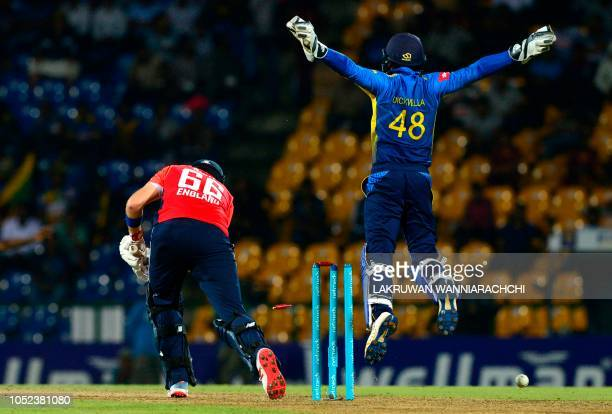 England cricketer Joe Root gets dismissed by Sri Lankan cricketer Amila Aponso as wicketkeeper Niroshan Dickwella looks on during the third one day...