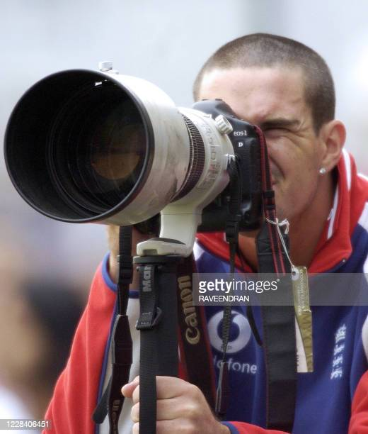 England cricketer Kevin Pietersen watches through a photographer's camera during the second day of the second Test match between India and England at...