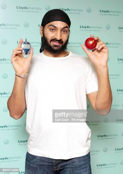 England cricketer Monty Panesar holds up a cricket ball and a plastered finger after having a diabetes test at the Lloydspharmacy Vauxhall London as...