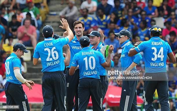England cricketer Steven Finn celebrates with his teammates after he dismissed Sri Lankan cricketer Angelo Mathews during the sixth One Day...