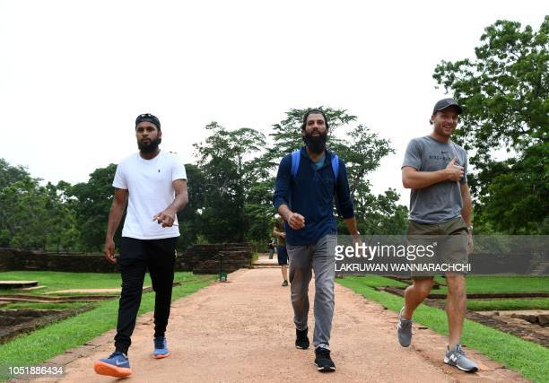 England cricketers Jos Buttler Moeen Ali and Adil Rashid walk from the 80metre ancient rock fortress of Sigiriya in northcentral Sri Lanka on October...