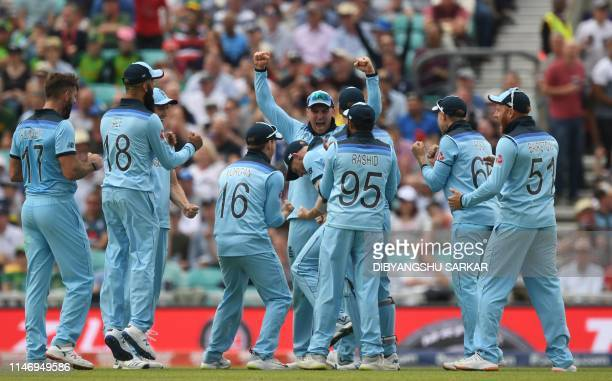 England cricketers led by Jason Roy celebrate after the run-out of South Africa's Dwaine Pretorius by teammate Ben Stokes during the 2019 Cricket...