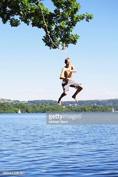 England, Cumbria, Windermere, boy (11-13) jumping into lake