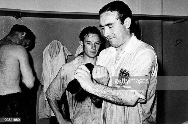 England defender Alf Ramsey squeezes the water out of his socks, watched by Johnny Berry, in the dressing-room after the International match between...