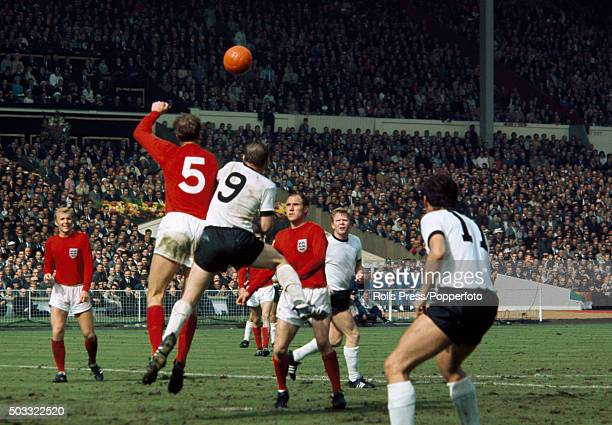 England defender Jack Charlton heads away from Uwe Seeler of West Germany watched by Bobby Moore Ray Wilson Helmut Haller and Lothar Emmerich during...