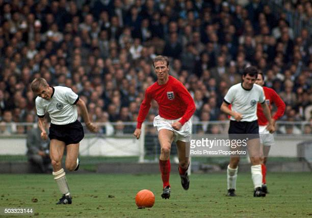 England defender Jack Charlton moves forward with the ball watched by Siegfried Held and Lothar Emmerich of West Germany during the FIFA World Cup...