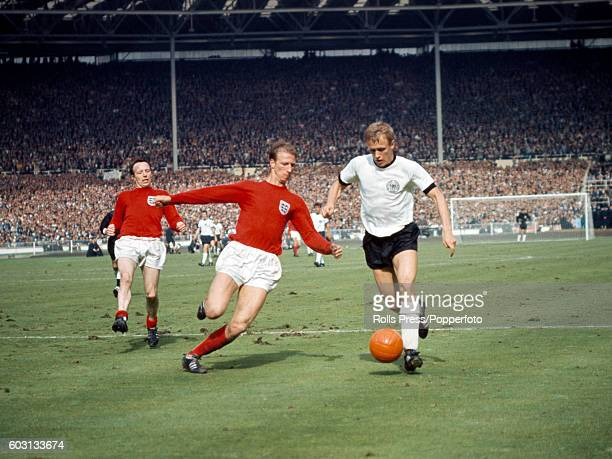 England defender Jack Charlton tackles Siegfried Held of West Germany watched by Nobby Stiles during the World Cup Final against West Germany at...