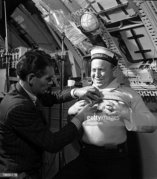 England Denham makeup artist Bob Lawrance applies an artificial tattoo on the chest of actor James Hayter who is playing the part of a seaman on the...