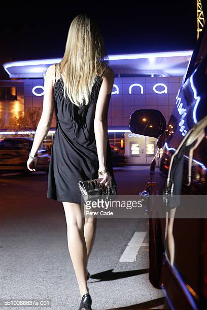 England, Devon, young woman walking through carpark towards night club, rear view