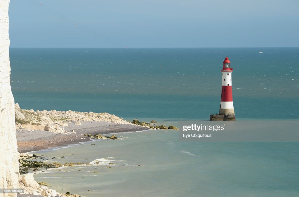 England, East Sussex, Beachy Head, Red and white painted lighthouse at base of cliffs. : Foto jornalística