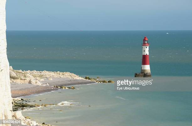 England East Sussex Beachy Head Red and white painted lighthouse at base of cliffs