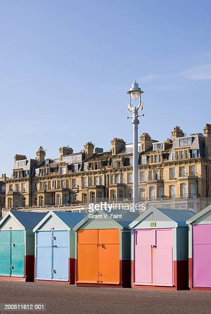 england, east sussex, brighton, row of painted beach huts - hut stock pictures, royalty-free photos & images