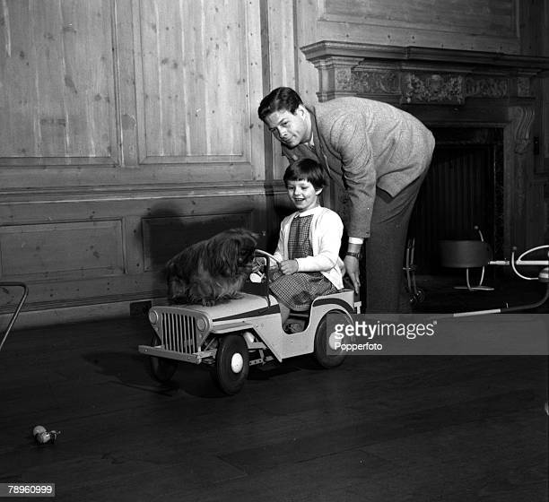 England ExKing Michael of Romania is pictured pushing his eldest daughter Princess Margaret and their pet dog in a toy car