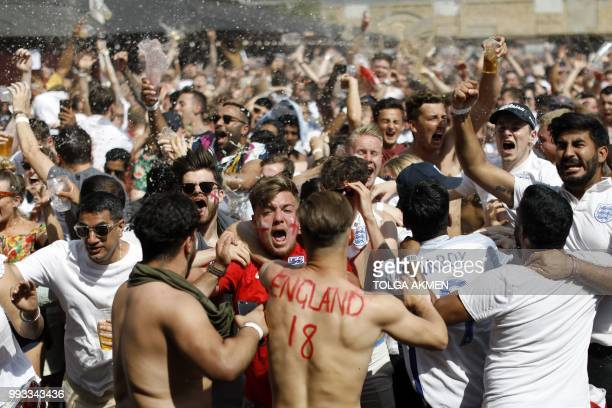 England fans celebrate as England's defender Harry Maguire scores the opening goal as they watch the Russia 2018 World Cup quarterfinal football...