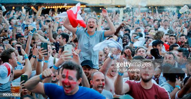 England fans celebrate England's opening goal scored by England's striker Harry Kane from the penalty spot as they watch the Russia 2018 World Cup...