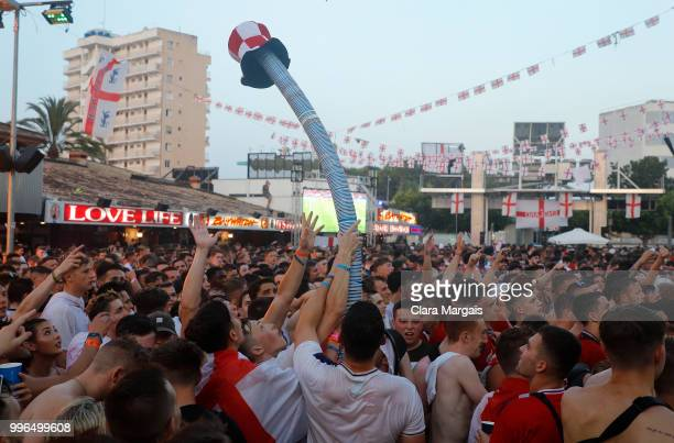 England fans create a beer snake using empty beer glasses as they gather to watch the World Cup semifinal match against Croatia in an open viewing...
