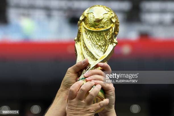 TOPSHOT England fans hold a replica of the World Cup trophy before the Russia 2018 World Cup semifinal football match between Croatia and England at...