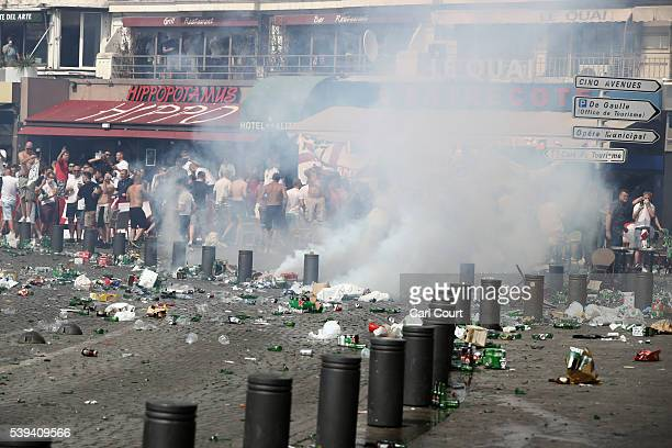 England fans react after police sprayed tear gas during clashes as rubbish lines the streets ahead of the game against Russia later today on June 11...