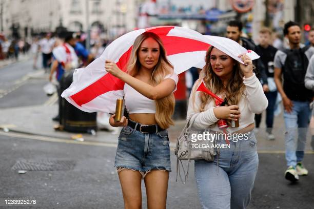 England fans shelter from the rain under flags ahead of the UEFA EURO 2020 final football match between England and Italy in central London on July...