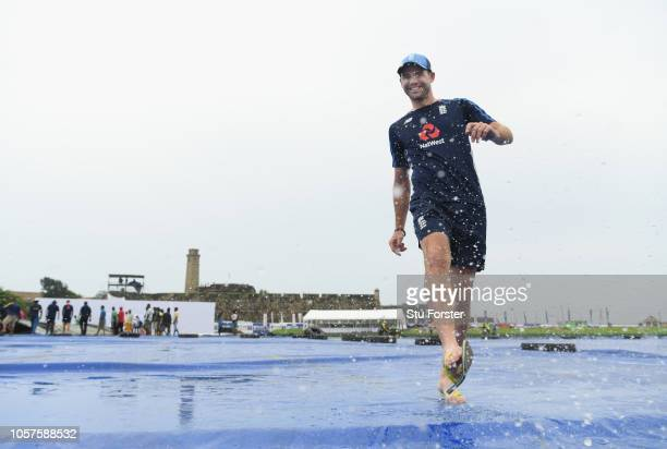 England fast bowler James Anderson enjoys the puddles on the outfield covers as practice is delayed due to the weather during England Cricket Nets at...
