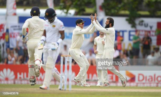 England fielder Jos Buttler celebrates with bowler Moeen Ali after Ali had caught and bowled Sri Lanka batsman Dimuth Karunaratne during Day Four of...