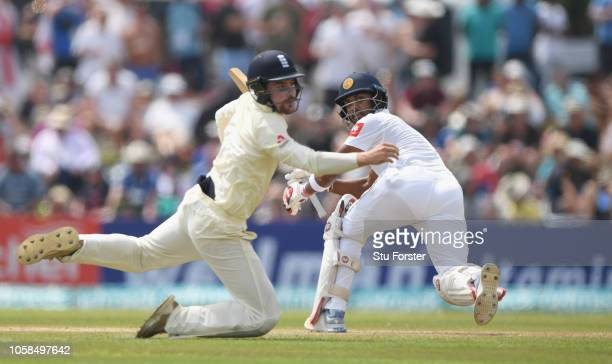 England fielder Rory Burns dives as Sri Lanka batsman Dinesh Chandimal sweeps for some runs during Day Two of the First Test match between Sri Lanka...