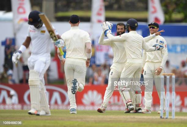 England fielders celebrate with bowler Moeen Ali after Ali had caught and bowled Sri Lanka batsman Dimuth Karunaratne during Day Four of the First...
