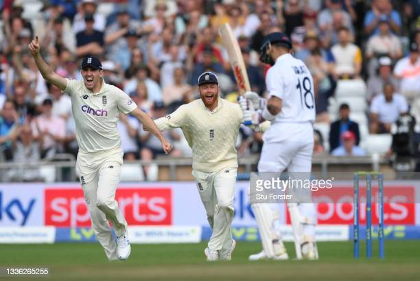 England fielders Craig Overton and Jonny Bairstow celebrate after bowler James Anderson had taken the wicket of Virat Kohli during day one of the...