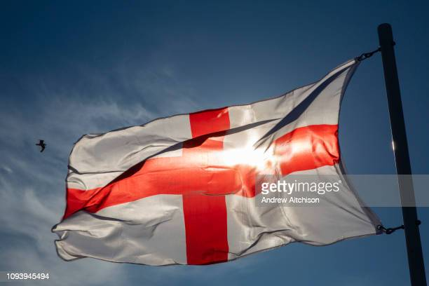 England Flag the Saint Georges Flag flying against a blue sky with the sunshine coming through it Folkestone Kent United Kingdom