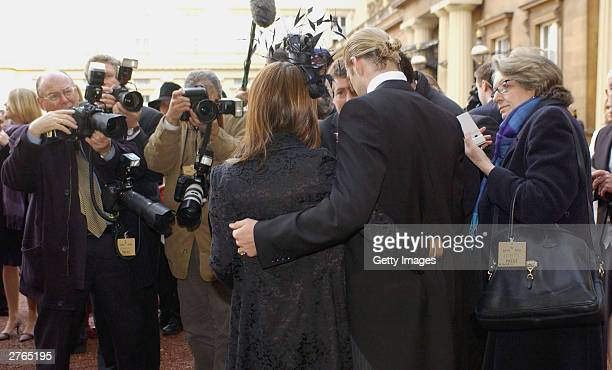 DAYS England football captain David Beckham and his wife Victoria meet the press after he received an OBE he received from Britain's Queen Elizabeth...