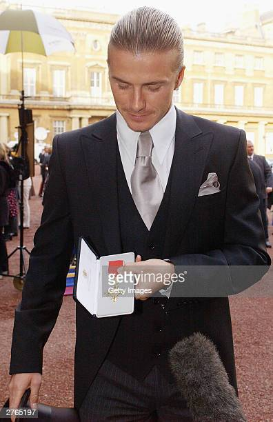 DAYS England football captain David Beckham shows off the OBE he received from Britain's Queen Elizabeth II at Buckingham Palace on November 27 2003...
