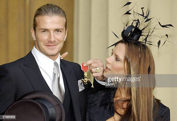 England football captain David Beckham stands with his wife Victoria as he shows off the OBE he received 27 November from Britain's Queen Elizabeth...