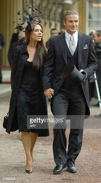 England football captain David Beckham walks with his wife Victoria after he received an OBE 27 November 2003 from Britain's Queen Elizabeth II at...