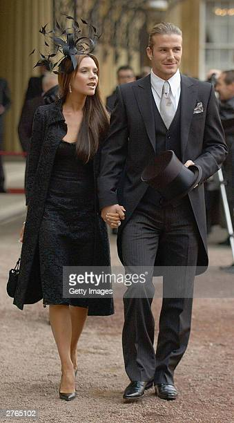 DAYS England football captain David Beckham walks with his wife Victoria as he shows off the OBE he received from Britain's Queen Elizabeth II at...
