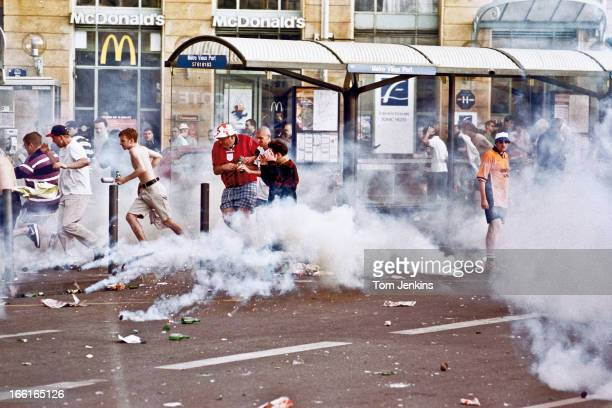 England football fans flee teargas canisters during a riot the day before England started their FIFA World Cup campaign in Marseille France on June...