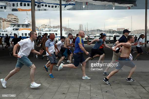England football fans run toward other football fans as England fans clash with police and local football supporters in Marseille on June 10 2016 in...
