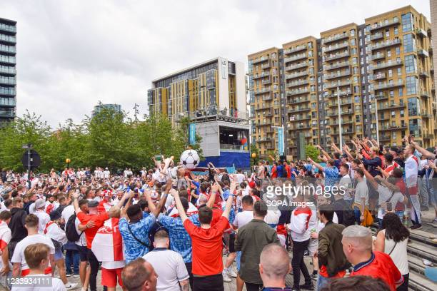 England football fans sing and throw around a large inflatable football outside Wembley Stadium ahead of the England v Italy Euro 2020 final.