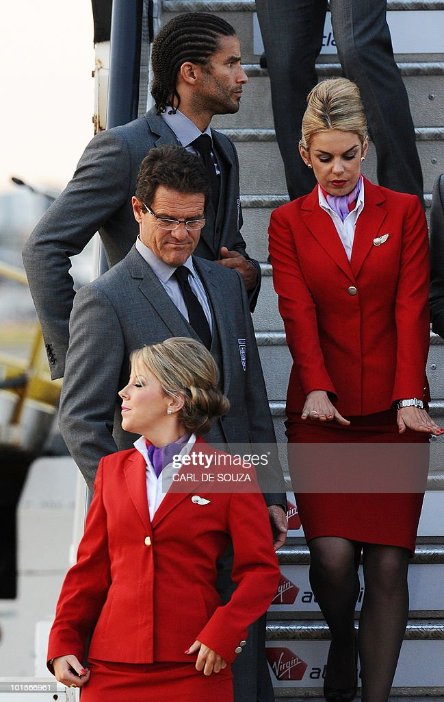 England football Manager Fabio Capello looks at an air stewardess before boarding a plane for South Africa at Heathrow airport, London, on June 2, 2010.