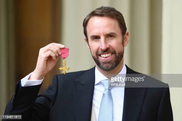 England football manager Gareth Southgate poses with his OBE for services to football following an investiture ceremony at Buckingham Palace on April...