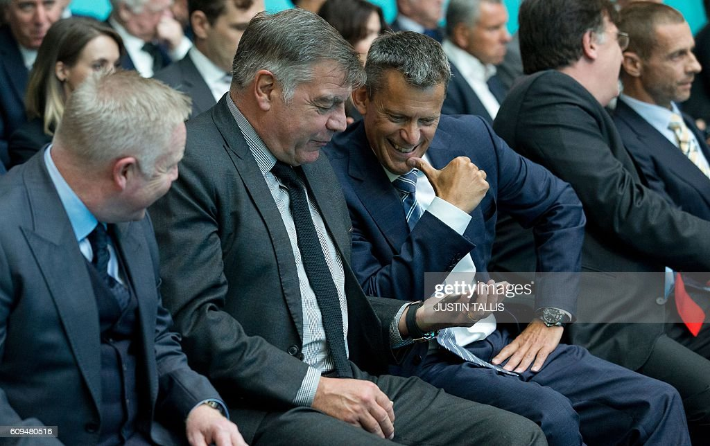 England football manager Sam Allardyce (Centre L) and English Football Association (FA) chief executive Martin Glenn (Centre R) sit looking at a phone ahead of an event to launch the logo for the 2020 UEFA European Championship football tournament in London on September 21, 2016. The 2020 UEFA European Championship will see matches hosted in 13 cities across Europe, with the semi-finals and final staged at Wembley Stadium in London in July 2020. / AFP / JUSTIN