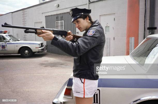 England football star Gary Lineker dressed in policeman's jacket and hat and holding a rifle pictured durinng a visit to a police station in Colorado...