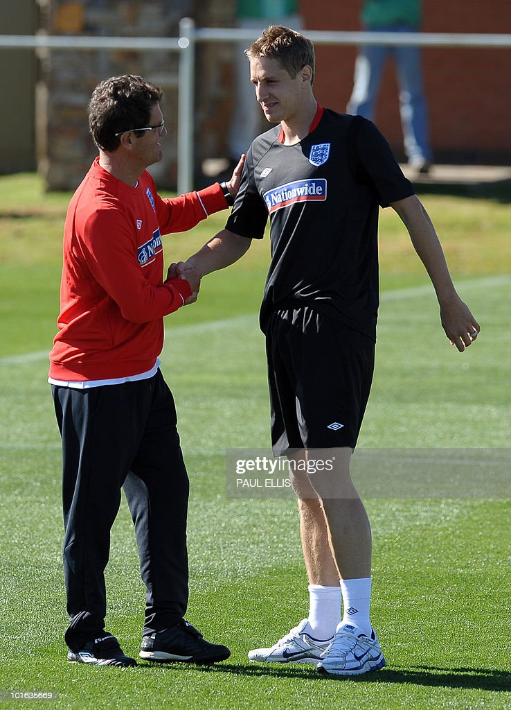 England football team manager Fabio Capello (L) welcomes replacement defender Michael Dawson as he arrives for a training session at the Royal Bafokeng Sports Campus near Rustenburg on June 5, 2010. Dawson was flown from England to replace captain Rio Ferdinand after he injured his knee during the team's first training session in the country.
