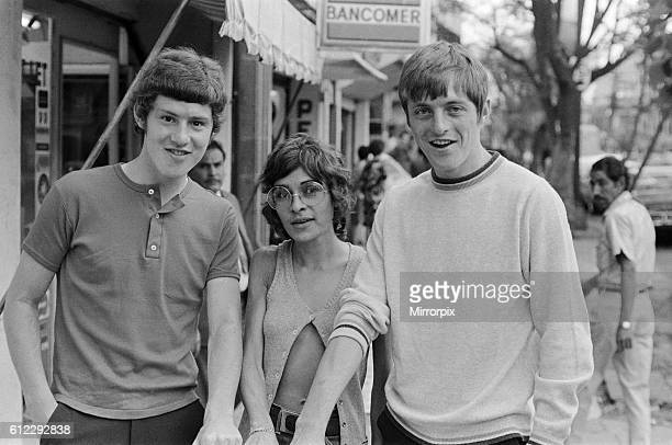 England footballer Brian Kidd and Allan Clarke pose with a woman showing off their tanned arms as the team stroll around the Zona Rosa part of Mexico...