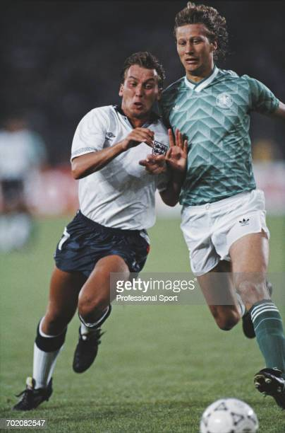 England footballer David Platt leans in to tackle German defender Guido Buchwald during the 1990 FIFA World Cup semi final match between West Germany...