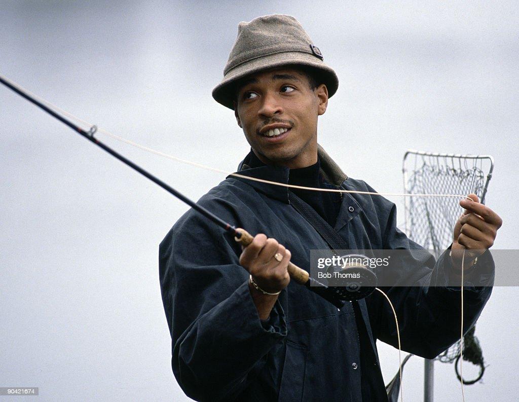 England footballer Des Walker enjoying trout fishing at Ravensthorpe reservoir in Northamptonshire, circa 1990.