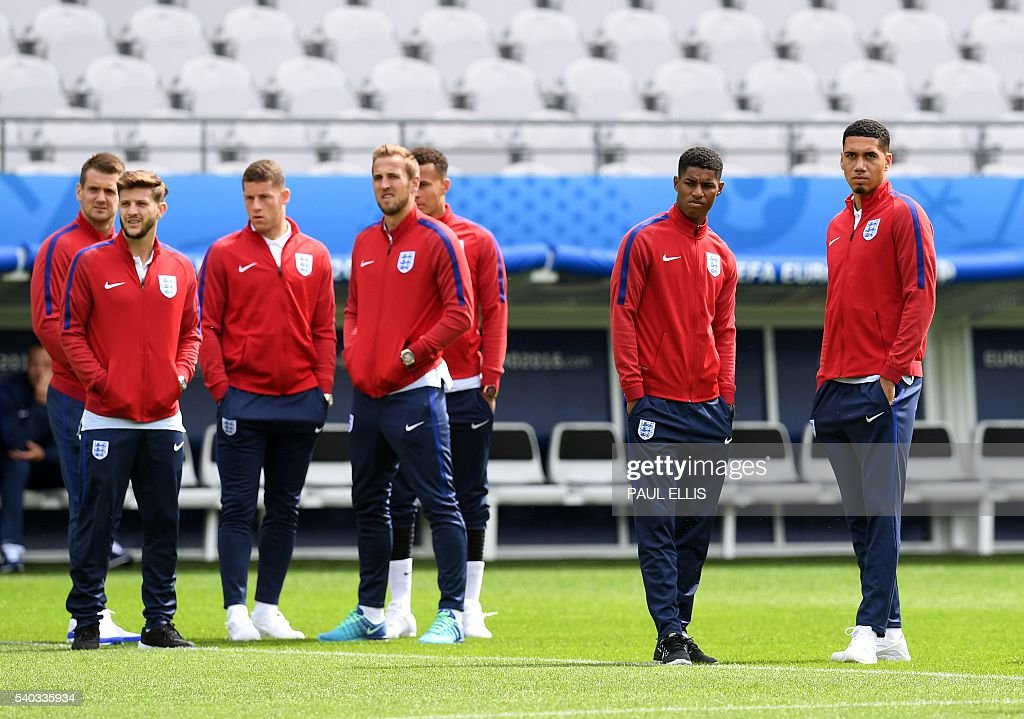 England forward Marcus Rashford (2nd R), England defender Chris Smalling (R) and their teammates walk on the pitch in Lens, France on June 15, 2016 during a pitch walkabout of the Euro 2016 football tournament. England prepares to face Wales on June 16, 2016. / AFP / PAUL