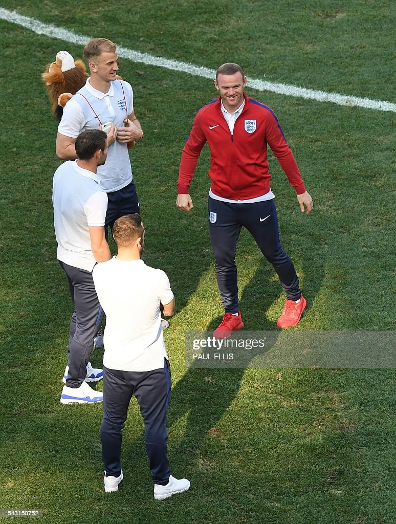 England forward Wayne Rooney (R) talks to England goalkeeper Joe Hart, England midfielder James Milner and England midfielder Jack Wilshere in the stadium in Nice, France on June 26, 2016 during the Euro 2016 football tournament. / AFP / PAUL