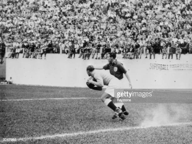 England goalkeeper Bert Williams holds the ball while his teammate Alf Ramsey stands ready to help during the EnglandUSA match on June 29 1950 in...