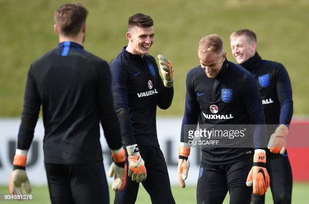 England goalkeepers Jack Butland Nick Pope Joe Hart Jordan Pickford react during a training session at St George's Park in BurtononTrent on March 20...